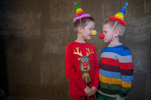 Two Boys Brothers In Bright Festive Attire Are Holding Pumpkins In Their Hands. Children Dictate Their Message To Santa Claus Before Christmas. Pupils Sing Songs And Talk About Successful Studies