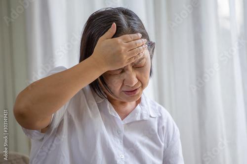 Asian senior woman sitting on sofa having headache at home Fototapete