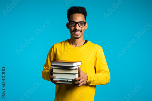 African student on blue background in the studio holds stack of university books from library Tableau sur Toile