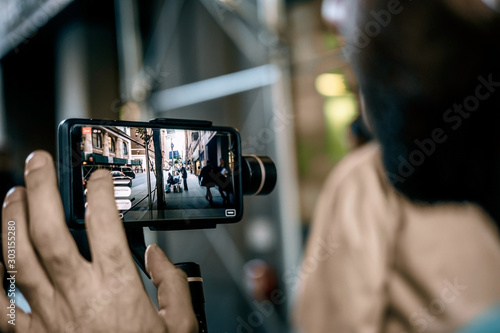 Fotografiet  Man using phone with stabilizer and taking pictures and live video in New York city