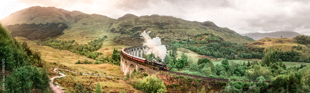 Fototapeta Glenfinnan Railway Viaduct with Jacobite steam train passing over. Harry Potter famous Glenfinnan viaduct, Scotland in cloudy weather with steam train.