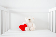Smiling White Teddy Bear Sitting On Baby Bed. Soft Red Heart Shape. Front View. Closeup.