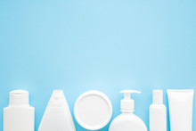 Different White Toiletries On Light Pastel Blue Table. Care About Face, Hands, Legs And Body Skin. Women Beauty Products. Empty Place For Text Or Logo. Flat Lay. Top Down View.