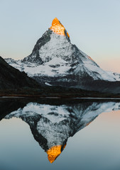 Obraz na Szkle Góry Alpenglow on iconic mountain peak Matterhorn in Swiss Alps, reflected in tranquil lake Riffelsee on high altitude. Unique travel destination in Alps. The beauty of nature simplicity concept.