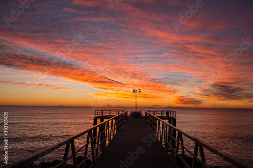 sunrise on the mediterranean sea with pier silhouette