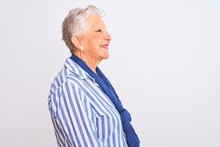 Senior Grey-haired Woman Wearing Blue Striped Shirt Standing Over Isolated White Background Looking To Side, Relax Profile Pose With Natural Face With Confident Smile.