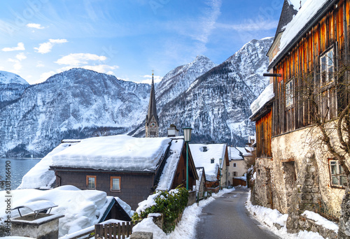 Classic postcard view of famous Hallstatt lakeside town in the Alps with traditional passenger ship on a beautiful cold sunny day with blue sky and clouds in winter, Salzkammergut region, Austria #303166490