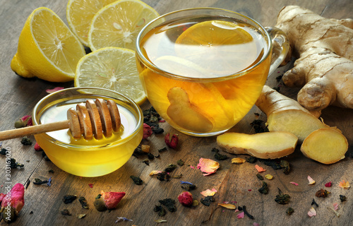 Recess Fitting Tea honey, lemon, ginger and a cup of tea with lemon on a wooden table. traditional cold remedies