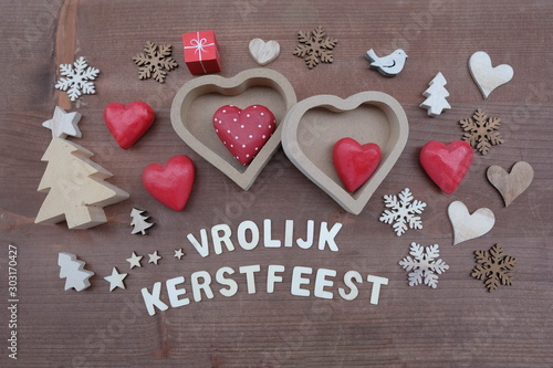 Photo Vrolijk Kerstfeest, Dutch Merry Christmas composed with wooden ornaments over wo