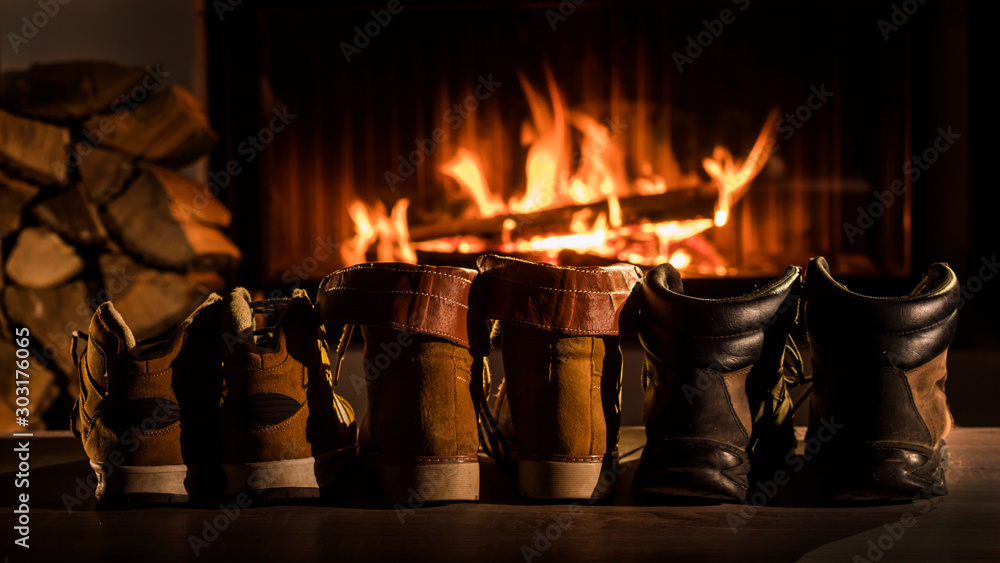 Fototapeta A few pairs of winter shoes are drying near the fireplace where the fire is on