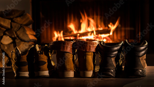 Obraz A few pairs of winter shoes are drying near the fireplace where the fire is on - fototapety do salonu