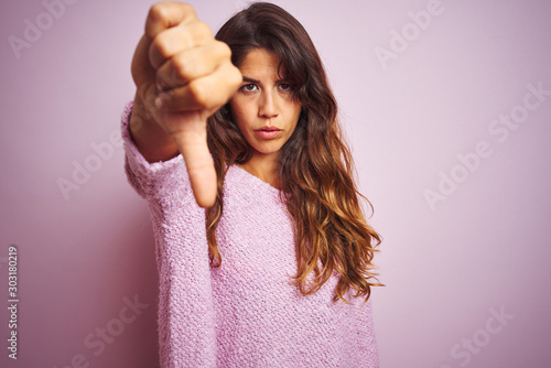 Fototapeta Young beautiful woman wearing sweater standing over pink isolated background looking unhappy and angry showing rejection and negative with thumbs down gesture. Bad expression. obraz
