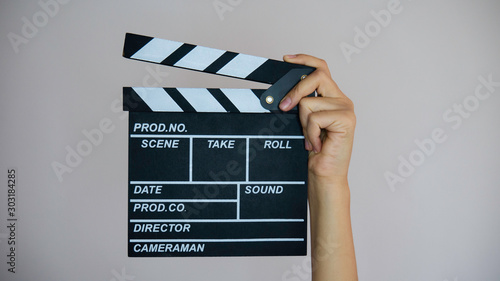 Vászonkép Female hands holding movie clapper isolated on gray background.