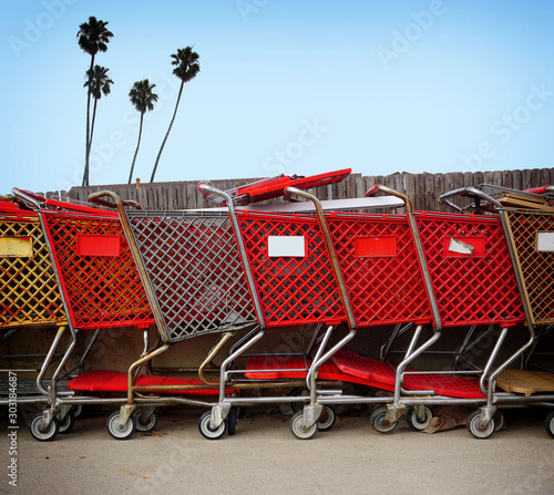 Old shopping carts lined up with palm trees #303184687