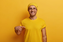 Half Length Shot Of Cheerful Man Points At Mockup Yellow T Shirt, Shows Space For Your Design, Has Glad Expression, Advertises New Outfit, Poses Against Bright Background. Look At This T Shirt
