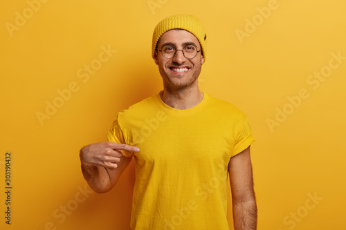 Half length shot of cheerful man points at mockup yellow t shirt, shows space for your design, has glad expression, advertises new outfit, poses against bright background Canvas-taulu