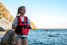 Young Girl In Red Life Jacket Stands On The Beach On Background Rock And Sea With Waves. Female Lifeguard On Duty On On The Ocean Coast.  Water Safety Concept. Rescuer Woman Watches The Seashore.