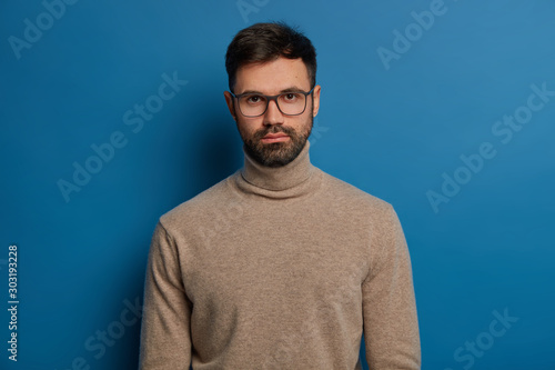 Portrait of serious handsome male has dark hair, thick bristle, looks straightly at camera, wears optical glasses and turtleneck jumper, isolated over blue background, listens attentively interlocutor