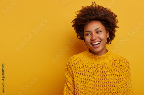 Obraz Tender charming happy curly woman has relaxed joyful face expression, Afro hairstyle, wears knitted sweater, laughs enthusiastic, poses against yellow background, blank space aside, turns away - fototapety do salonu