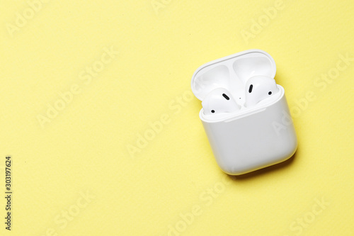 Cuadros en Lienzo  Wireless headphones on a yellow background with place for text.