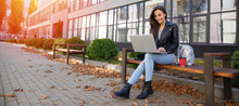 Freelancer Girl. Full-length Photo Of Attractive Woman In Casual Outfit, Who Is Smiling, Sitting On A Bench In The City With Her Laptop And A Red Coffee Cup.