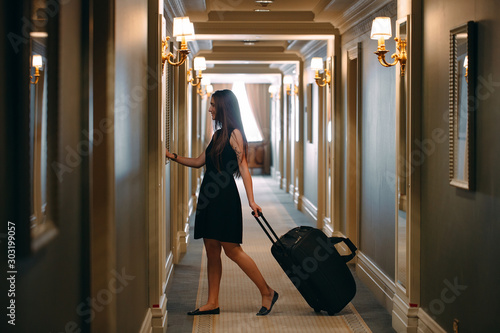 Cuadros en Lienzo  Young woman with handbag and suitcase in an elegant suit walks the hotel corridor to her room
