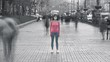The woman with medical face mask stands in the crowded city. time lapse