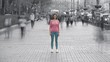 The woman is standing on the sidewalk against the human flow. time lapse