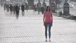 The girl is standing on the sidewalk against the human flow. time lapse
