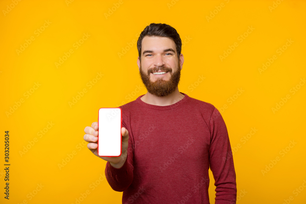 Fototapeta Photo of cheerful guy with beard and wearing red sweater, showing mobile screen at camera over yellow background
