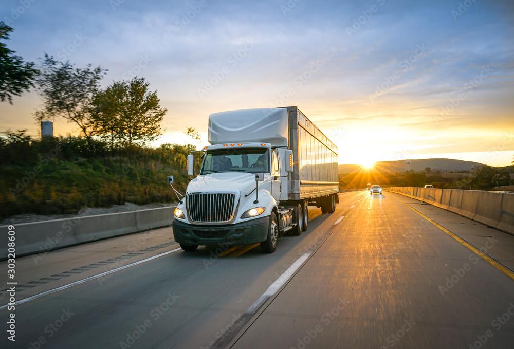 Fototapeta White semi-truck on the highway delivering freight
