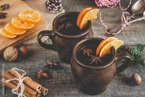 Poster de jardin Alcool Hot mulled wine with orange, cinnamon, honey and anise on wooden background.
