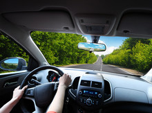 Car Dashboard With Driver's Hands On The Steering Wheel And Rear View Mirrors On A Road In Motion With Trees Against Sky With Clouds