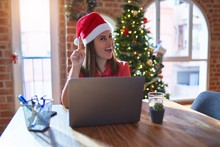 Beautiful Woman Sitting At The Table Working With Laptop Wearing Santa Claus Hat At Christmas Pointing Finger Up With Successful Idea. Exited And Happy. Number One.