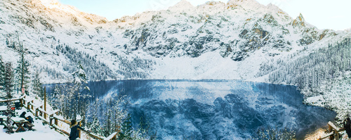 Fototapety, obrazy: Beautiful view of the crystal clear mountain lake in the Carpathians of the Tatra Mountains with people relaxing on the observation deck. A cold sunny day with blue sky.