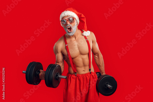 Fotografía  Brutal and strong Santa Claus training with dumbbell