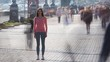 The female is standing on the pavement against the human flow. time lapse