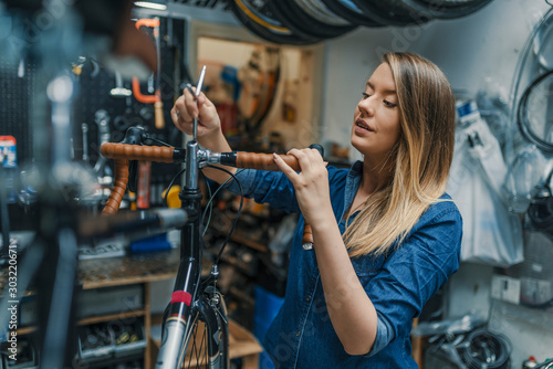 Fotografía  Woman bicycle mechanic is repairing a bike in the workshop