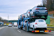 Car carrier transporter truck on road. Auto vehicles hauler on driveway. European transport logistics at haulage work transportation. Heavy haul trailer with driver on highway.