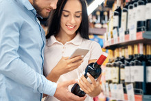 Daily Shopping. Couple In The Supermarket Together At Alcohol Department Hugging Choosing Wine Woman Scanning Qr Code On Smartphone Happy Close-up