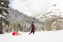 Beautiful, Happy, Smiling Young Woman Wearing Winter Fashions A Wool Coat, Hat, Gloves And Snow Boots Pulling A Wooden Sled With Christmas Gifts Presents In A Snowy Alpine Mountain Landscape