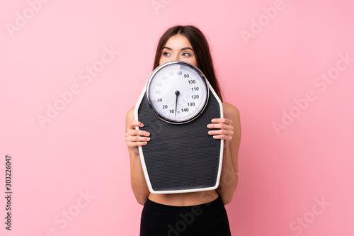Pretty young girl with weighing machine over isolated pink background with weighing machine and hiding behind it
