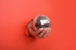 Leinwandbild Motiv Hand holding Silver disco mirror ball on torn red paper wall. Copy space aside for your advertising and offer or sale content.