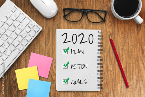 Платно New Year Resolution Goal List 2020 - Business office desk with notebook written in handwriting about plan listing of new year goals and resolutions setting