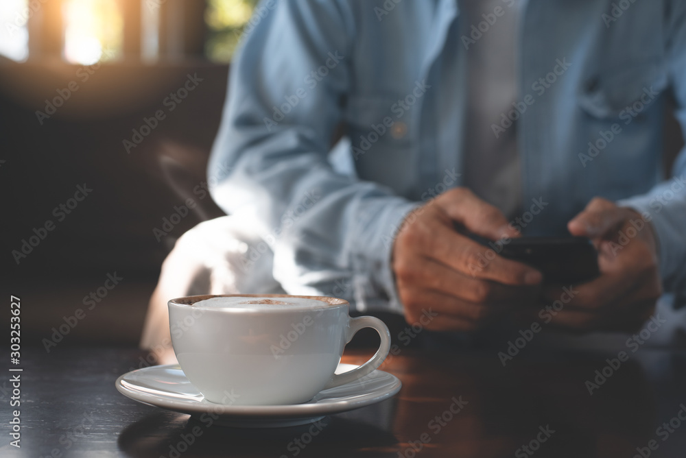 Fototapeta Man using mobile phone and coffee
