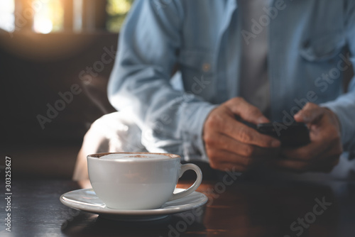 Obraz Man using mobile phone and coffee - fototapety do salonu