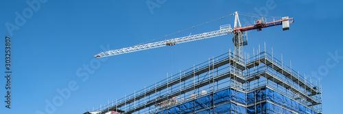 Construction crane on a highrise building construction site. Gos Fototapet