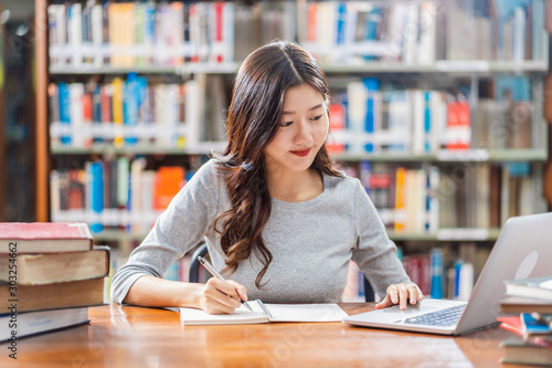 Fototapeta Asian young Student in casual suit doing homework and using technology laptop in
