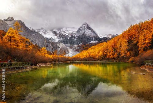 Fotografija  Panorama of Pearl Lake with the holy snow mountain in autumn season in yading nature reserve, Daocheng County, southwest of Sichuan Province, China
