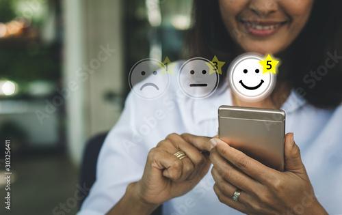 Fotografía  Businesswoman pressing face emoticon on virtual touch screen at smartphone